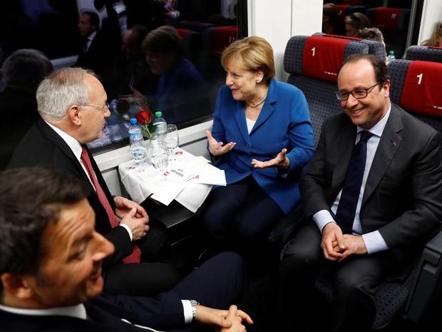 O premiê italiano Matteo Renzi e o presidente suíço Johann Schneider-Ammann conversam com a chanceler alemã Angela Merkel e o presidente francês François Hollande durante viagem inaugural pelo túnel de São Gotardo nesta quarta-feira (1º) na Suíça (Foto: REUTERS/Peter Klauzner/Pool)