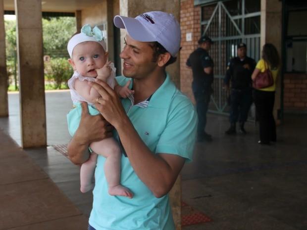 Pai e bebê aguardam esposa na saída do exame da OAB (Foto: Graziela Rezende/G1 MS)