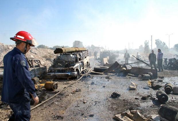 Bombeiros são vistos em local de explosão em Hana, na Síria, neste domingo (20) (Foto: Sana/AFP)