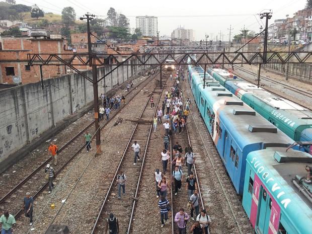 Passageiros andam na via após problema com trem da Supervia na Estação Mangueira, na manhã desta quinta-feira (20) (Foto: Beethoven Lima/VC no G1)