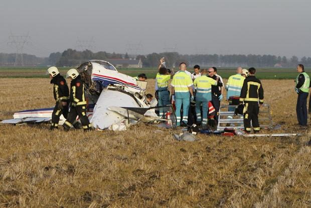 Equipes observam destroços de um de dois aviões de pequeno porte que se chocaram no ar nesta segunda-feira (22) em Dronten, na Holanda. O acidente matou duas pessoas e deixou dois feridos, segundo a imprensa local (Foto: AFP)