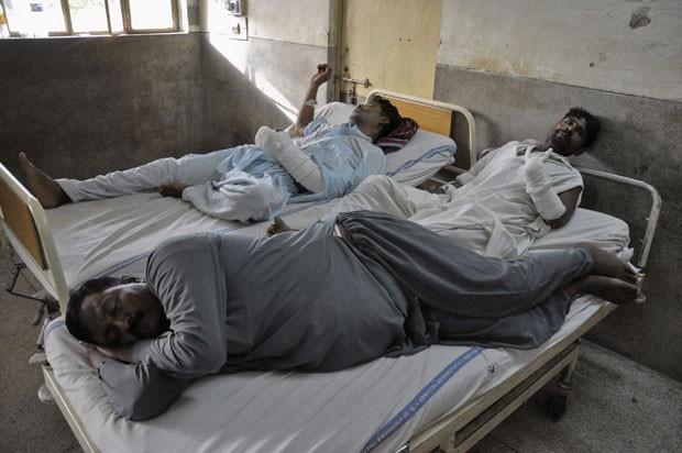 Ghulam Mustafa, de 38 anos, e Liaquat Ali, de 42 anos, são vistos em hospital após terem a mão esquerda cortada (Foto: K. Chaudhry/Reuters)