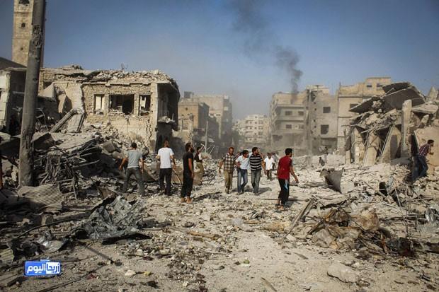 Imagem fornecida pelo grupo antigoverno Ariha Today mostra pessoas andando nos destroços de queda de caça do governo sírio sobre um mercado da cidade nesta segunda-feira (3) (Foto: Ariha Today via AP)