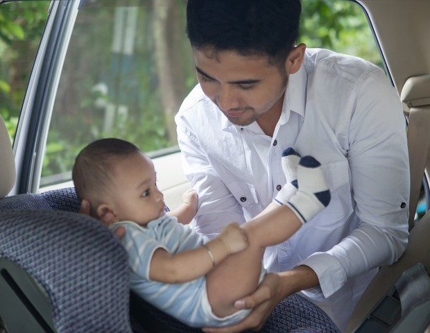 Portrait of a father lifting his newborn baby from the car seat (Foto: Getty Images/iStockphoto)