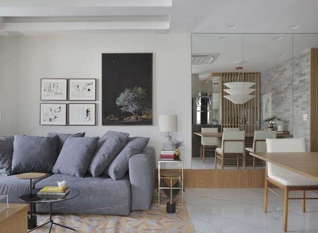 LIVING | Na sala de estar, integrada ao jantar, o tapete, da Square Foot, separa visualmente os ambientes.  Sofá, da Arquivo Contemporâneo. Mesas de centro e lateral, assinadas por Jader Almeida, à venda na Arquivo Contemporâneo. Na parede, conjunto de qu (Foto: Denilson Machado/MCA Estudio/Divulgação)