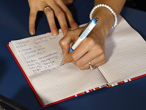 Bojana Danilovic escreve com o caderno de cabeça para baixo em seu escritório na cidade de Uzice, no sudoeste da Sérvia (Foto: Marko Djurica/Reuters)
