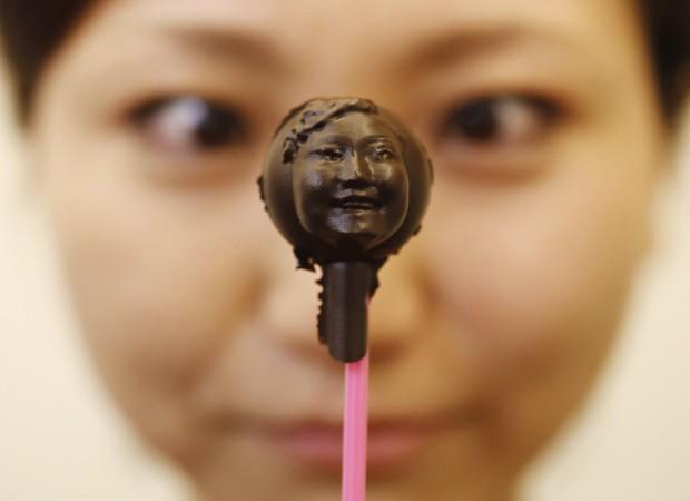 A japonesa Mariya Kawae, de 30 anos, observa um pirulito de chocolate moldado com a imagem de seu próprio rosto com ajuda de uma impressora 3D. O doce foi feito como parte de uma oficina de preparação de chocolates oferecida por um laboratório de design em Tóquio, no Japão. Os participantes da oficina puderam escanear imagens de seu rosto e transmiti-la para computadores, para então criar moldes de plástico com uma impressora 3D. O chocolate derretido foi derramado nos moldes para depois ficar com a forma das faces dos integrantes do evento, que foi gratuito e teve 20 participantes (Foto: Issei Kato/Reuters)