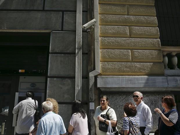Gregos fazem fila para caixa eletrônico em agência fechada do Banco Nacional, depois de o governo grego impor limite de saques diários até o dia 6 de julho (Foto: Alkis Konstantinidis/Reuters)