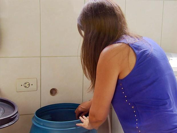 Moradora de São João da Mata reserva água em um tambor para uso (Foto: Carlos Cazelato / EPTV)