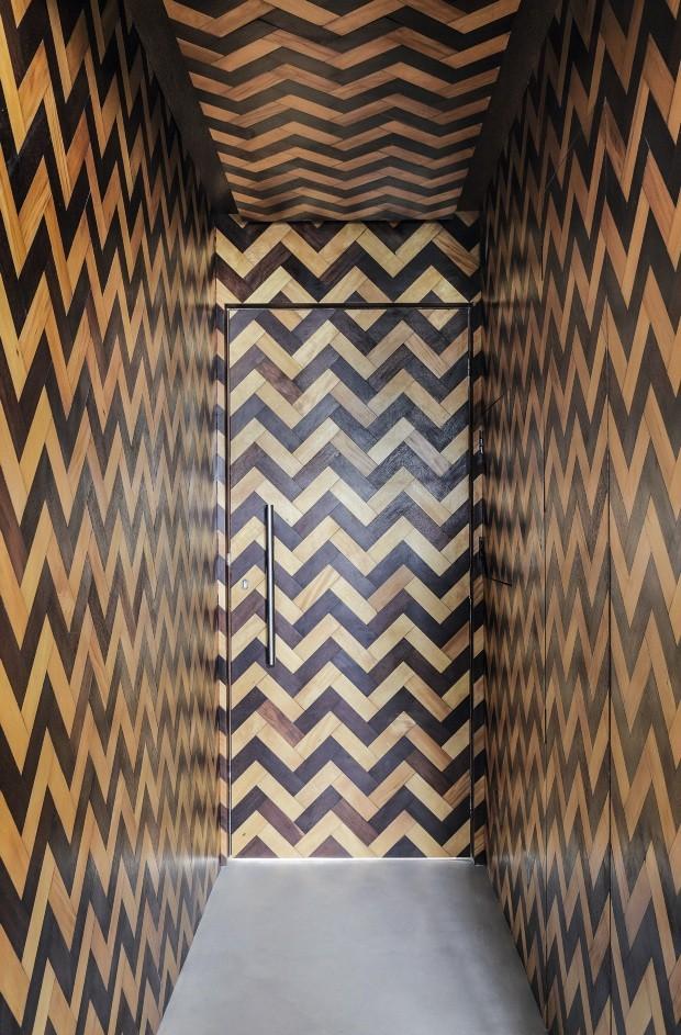 Hall de entrada. Concebido como um túnel do tempo, é revestido por tacos bicolores de sucupira e pau-marfim, trazidos da casa do avô do morador (Foto: Denilson Machado / MCA Estúdio / Divulgação)