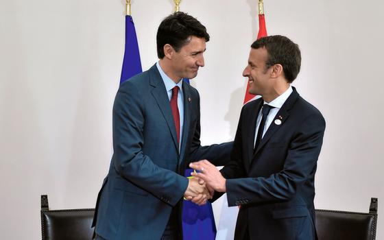 O primeiro ministro do Canadá,Justin Trundeau(á esq.)cumprimenta o presidente da França,Emmanuel Macrom,em encontro do G-7 (Foto: Stephane De Sakutin//REUTERS)