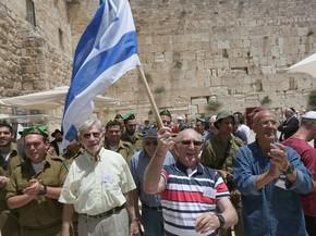 Grupo de judeus dança após cerimônia de Bar eMitzvah ser realizada nesta segunda-feira (2) no Muro das Lamentações, em Jerusalém (Foto: MENAHEM KAHANA / AFP)
