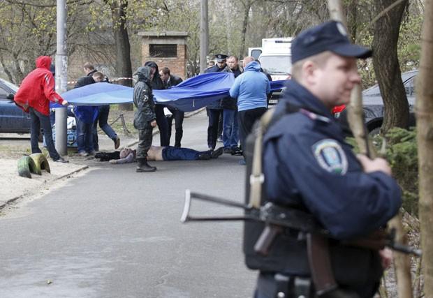Investigadores trabalham no local do assassinato do jornalista ucraniano Oles Buzina nesta quinta-feira (16) em Kiev (Foto: Valentyn Ogirenko/Reuters)