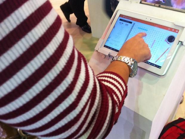 Mulher joga caça-palavras no tablet em estande da feira (Foto: Isabela Marinho/G1)