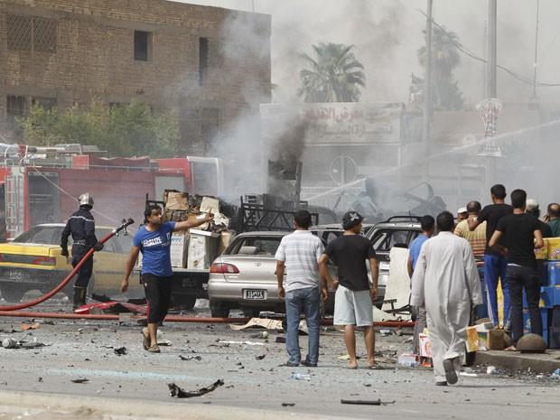 Locais se reúnem após explosão de dois carros-bomba no centro de Bagdá (Foto: Saad Shalash/Reuters)
