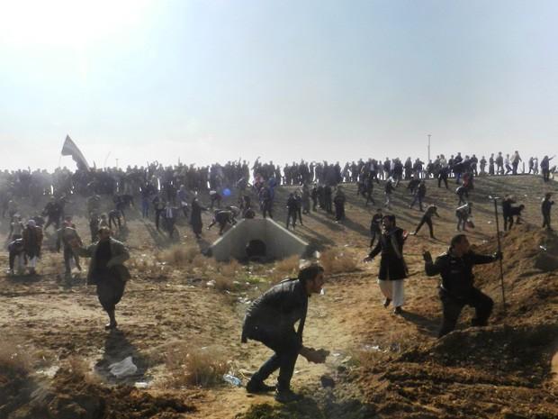 Iraquianos jogam pedras durante protesto em Ramadi (Foto: Azhar Shallal/AFP)