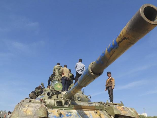 Menino observa com membros do Exército Livre da Síria o tanque capturado após vitória contra forças do governo em Salqin, perto de Idlib. (Foto: Reuters/Abu Baker Al-Shemali/Shaam News Network)