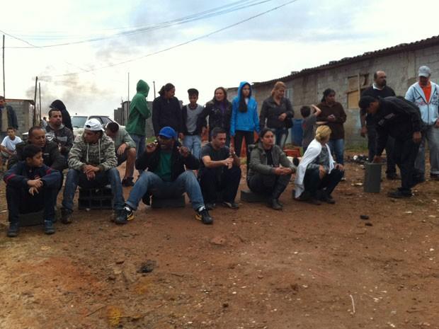 Moradores sentam para evitar passagem de policiais (Foto: Tatiana Santiago/G1)