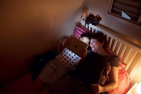 CUIDADO Karina e Clara, na cama. A menina, de 9 anos, não pode usar redes sociais e tem horário restrito para usar a internet  (Foto: Rogério Cassimiro/ÉPOCA)