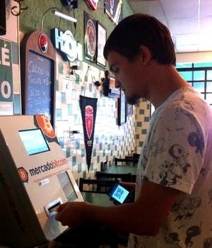 Ricardo Tavares troca dinheiro por bitcoin no caixa eletrônico do bar do Zé Gordo (Foto: Época Negócios)