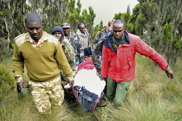 Bombeiros carregam um dos corpos encontrados no local do acidente (Foto: Peter Greste/Reuters)