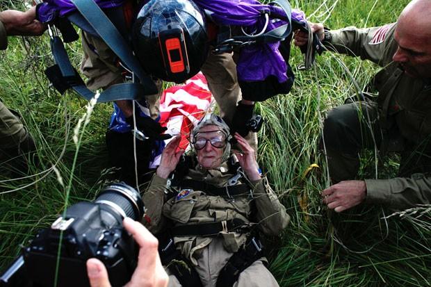 O veterano de guerra sentado após saltar de paraquedas nesta quinta-feira (5) (Foto: Thibault Camus/AP)