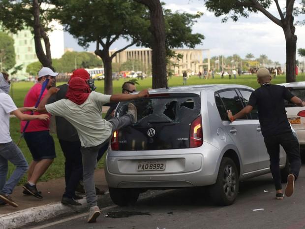Manifestantes quebram um carro estacionado na Esplanada dos Ministérios, em Brasília, durante protesto contra a PEC 55, que limita os gastos públicos para os próximos 20 anos (Foto: Eraldo Peres/AP)
