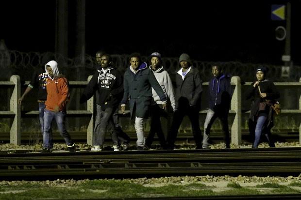Imigrantes andam nos trilhos do Eurotúnel perto de Calais, na França, na noite deste domingo (2) (Foto: Pascal Rossignol/Reuters)
