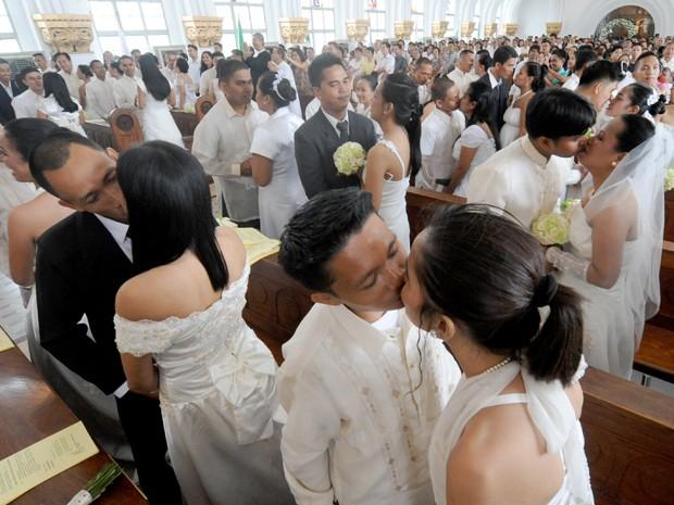 Noivos se beijam durante casamento coletivo na capela de uma universidade em Manila, nas Filipinas (Foto: AFP)