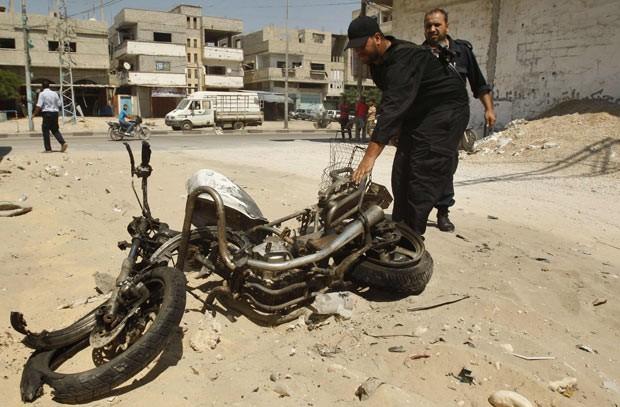 Policiais palestinos observam o que sobrou da moto atingida por ataque israelenese neste domingo (5) no sul da Faixa de Gaza (Foto: AFP)