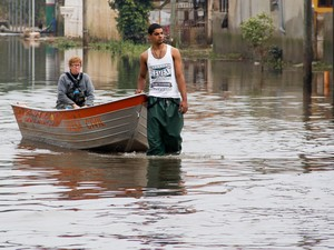 Barco da Defesa Civil passa por Alvorada, município da Região Metropolitana de Porto Alegre(RS), onde o nível da água começa a baixar. Os moradores deram início os trabalhos de limpeza após os prejuízos causados pelas chuvas nos últimos dias (Foto: Everton Silveira/Raw Image/Estadão Conteúdo)