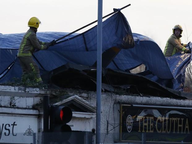 Destroços do helicóptero são retirados na manhã deste sábado (Foto: Russell Cheyne/Reuters)