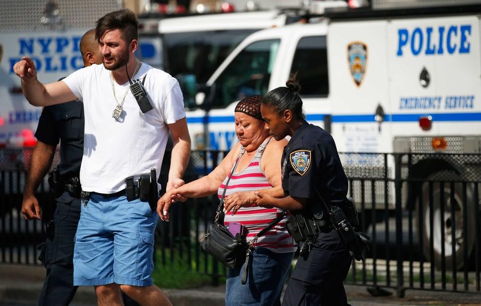 Policial ajuda a retirar pessoas da região do hospital em que atirador disparou nesta sexta-feira (30) em Nova York (Foto: REUTERS/Brendan Mcdermid)