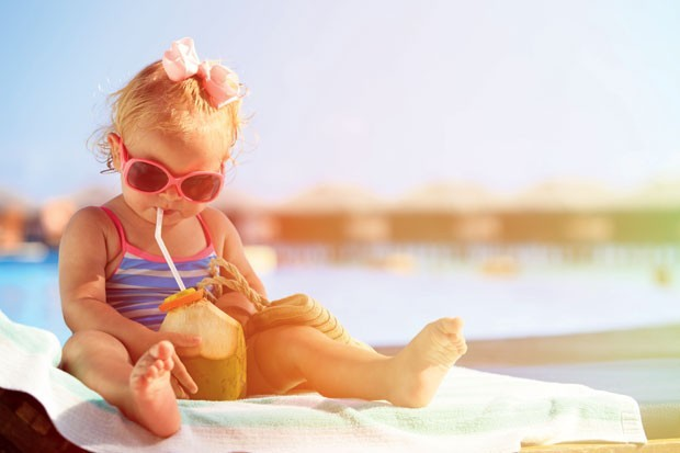 Bebê bebendo água de coco na praia (Foto: Thinkstock)