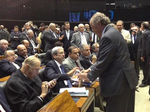 Parlamentares dividem pacotes de bolacha durante a sessão (Foto: Fernanda Calgaro / G1)
