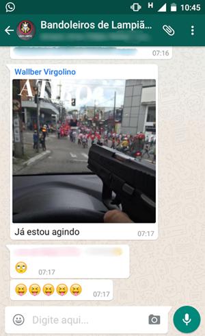 Foto mostra uma mão segurando uma arma apontada para um ato do MST com a pergunta 'Atiro?' (Foto: Reprodução/Whatsapp)