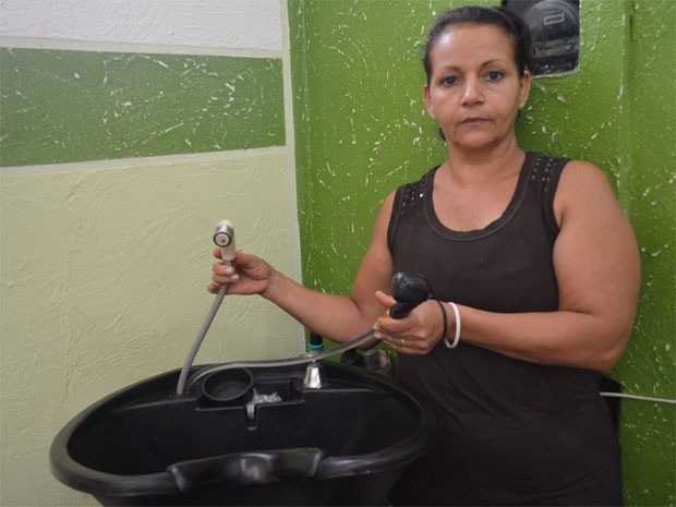 Isildinha de Jesus, de 54 anos, comprou uma caixa d'água para ajudar a abastecer o salão de beleza na Lagoinha (Foto: Adriano Oliveira/G1)