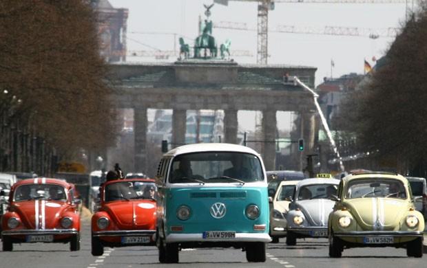 Uma kombi e fuscas antigos desfilam na frente do Portão de Brandemburgo, em Berlim; empresa criou um tour pela cidade nos carros da Volkswagen (Foto: Steffen Trumpf /AFP)