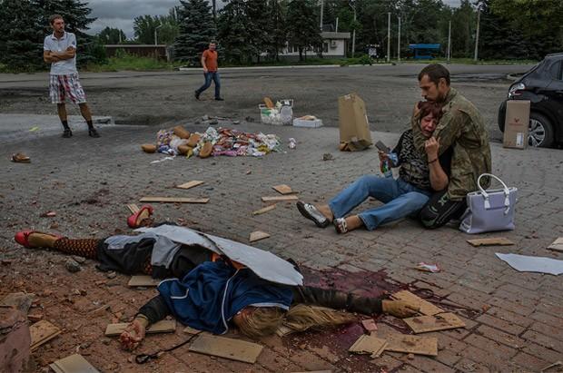 Mulher é amparada pelo filho, um rebelde pró-Rússia, em frente ao corpo da filha morta em uma manhã de bombardeio na guerra separatista na região de Donetsk, na Ucrânia. Foto de agosto de 2014 (Foto: Mauricio Lima/The New York Times/POY Latam 2015)