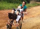 Mãe empurra cadeira de rodas para filha poder ir à escola (Genival Moura/G1)