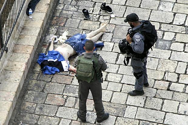 Policiais examinam corpo de palestino morto após esfaquear dois policiais no Portão de Damasco, em Jerusalém (Foto: Mahmoud Illean/AP)
