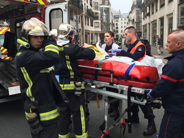 Pessoa ferida na sede da revista satírica 'Charlie Hebdo', em Paris, é socorrida após ataque a tiros deixar mais de 10 mortos e vários feridos (Foto: Philippe Dupeyrat/AFP)
