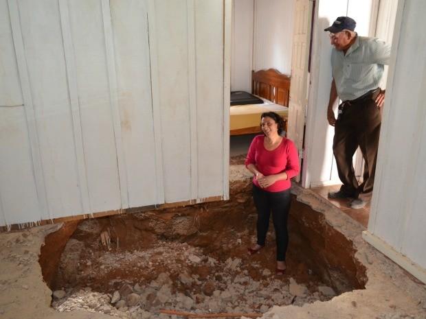 Buraco tinha cerca de dois metros de profundidade, de acordo com moradora, e foi parcialmente tapado.  (Foto: Lauane Sena/G1)