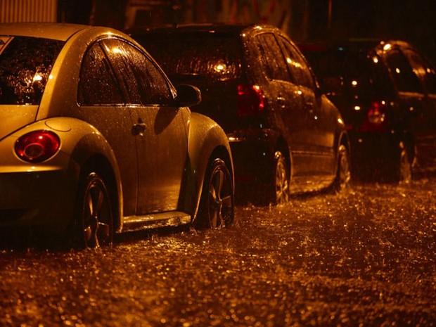 Pneus de veículos estacionados em rua inundada na Lapa ficaram parcialmente cobertos (Foto: Rodrigo Gorosito/G1)