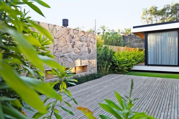 Área de contemplação. O jardim em frente ao living recebeu um deque de cumaru e uma lareira, da Construflama. Rente ao painel de pedras bolão, barba-de-serpente. Ao lado, pleomeles seguidas de alpínias (Foto: Julia Campos / Divulgação)