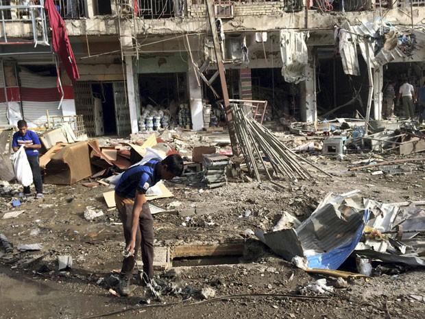Pessoas tentam reparar estragos causados por explosão em distrito de Bagdá neste domingo (8) (Foto: Khalid Mohammed/AP)