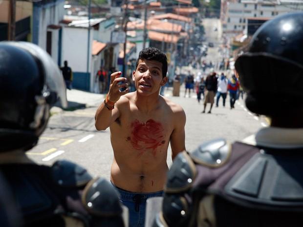 Um garoto com sangue no peito gesticula com policiais após Kluiver Roa, um estudante de 14 anos, ter sido morto em um protesto na cidade de San Cristobal, na Venezuela (Foto: Carlos Eduardo Ramirez/Reuters)