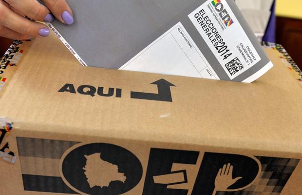 Funcionária de departamento eleitoral faz demonstração de voto em urna de La Paz, na Bolívia, neste sábado (11) (Foto: Cris Bouroncle/AFP)