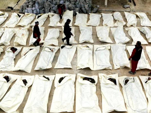 Funcionários documentam e contam corpos que, de acordo com combatentes rebeldes, são de membros das forças leais ao presidente da Síria Bashar al-Assad. Eles foram preparados para serem enterrados em Aleppo, no norte do país (Foto: Mahmoud Hebbo/Reuters)