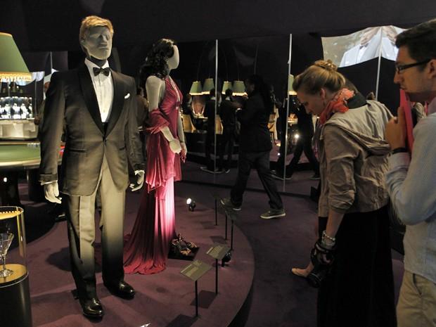 Visitantes olham para terno usado pelo personagem James Bond, vivido por Pierce Brosnan, no filme 'GoldenEye', em exposição em Londres (Foto: AP/Sang Tan)